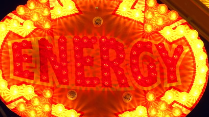"""energy"" sign lit up by light bulbs at night"