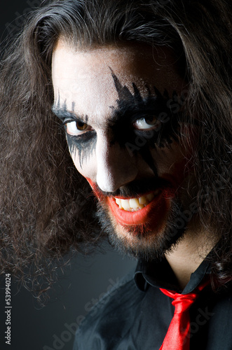 Joker personification with man in dark room
