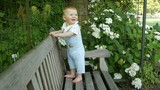 Cute little baby playing on a bench in the park