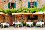 Cafe tables and chairs outside a stone building in Tuscany