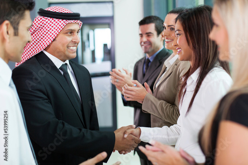 group of business team welcoming arabian businessman