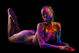 Brightly painted naked model isolated on black