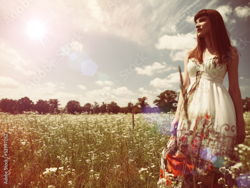 Beauty young woman walking around the summer meadow