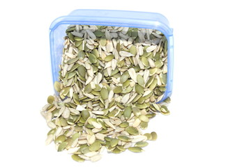 Pumpkin seeds spilling from container on a white background