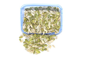 Pumpkin seeds spilling from container on white background