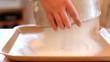 Girl sifts the flour through a sieve