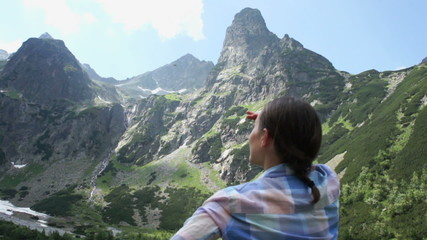 Woman at the mountain peak looking at beautiful view