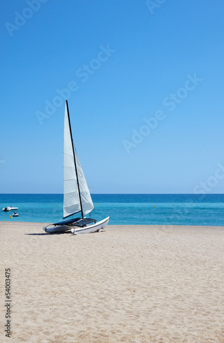White sailboat on perfect tropical white sand beach