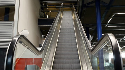 An escalator going up with no people on it.