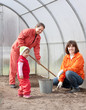 women with child works at hothouse