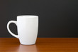 White mug on dark wooden table with black wall