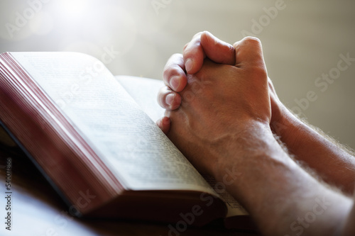 Leinwanddruck Bild Praying hands on a Holy Bible