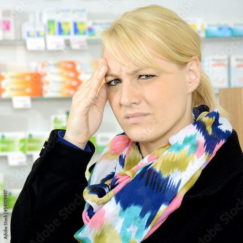 Frau mit Migräne in Apotheke