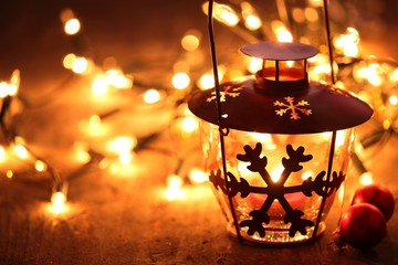 Lantern and Christmas lights burning in dark..