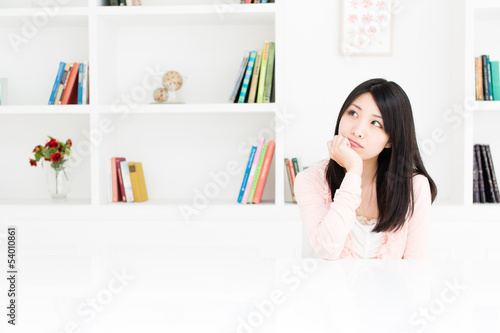 attractive asian woman thinking in the room