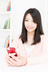 attractive asian woman using smart phone in the room