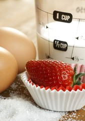 Cupcakes with strawberry, eggs and measuring cup with milk.