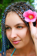 Portrait of attractive young woman with flower outdoor close-up