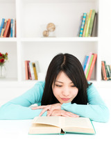 attractive asian woman reading book in the room