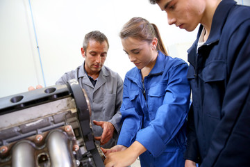 Students with instructor working on auto engine