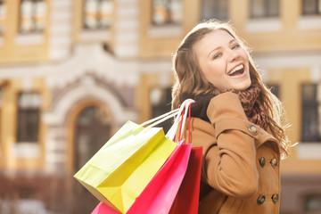 Young shopaholic woman. Beautiful young women holding the shoppi