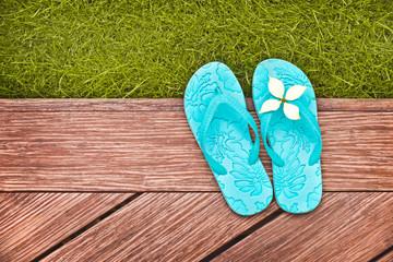 Sandales bleues, terrasse en bois et pelouse