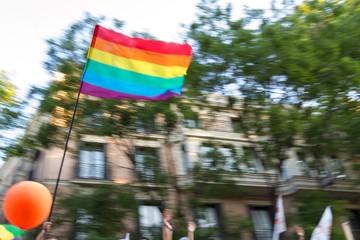 Gente aclamando el paso de la bandera gay