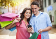 Young couple with shopping bag using mobile phone