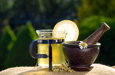 Tea and wooden pestle with chamomiles