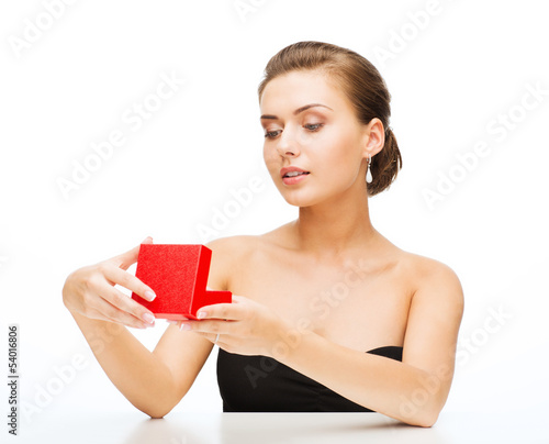 woman with earrings, wedding ring and gift box