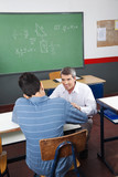 Teenage Boy Studying While Teacher Looking At Him