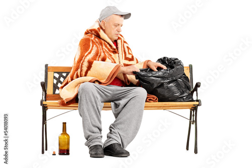 Homeless mature man sitting on a bench and looking for something