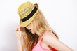 Funny blonde woman with straw hat isolated on white