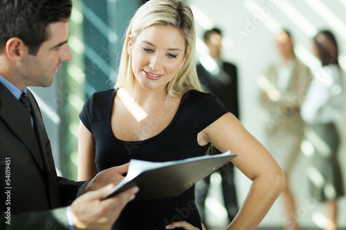 businessman and businesswoman looking at the document