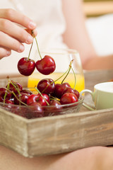 Hand holding a pair of cherries