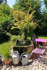 Gartenidylle mit Brunnen und pinkem Stuhl