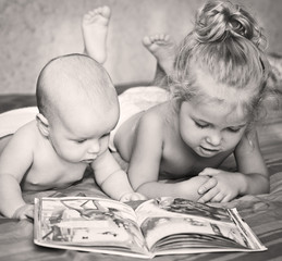 Little brother and sister looking at a book