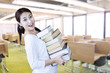 Attractive female student bring pile of books at library