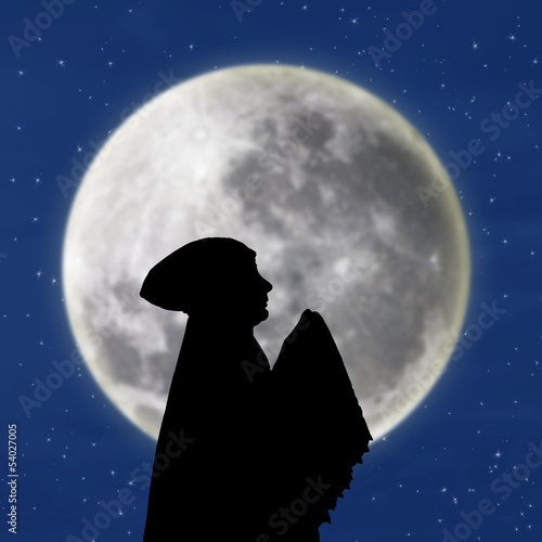 Female muslim praying under blue moon