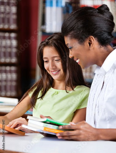 Librarian And Schoolgirl Looking Together At Book