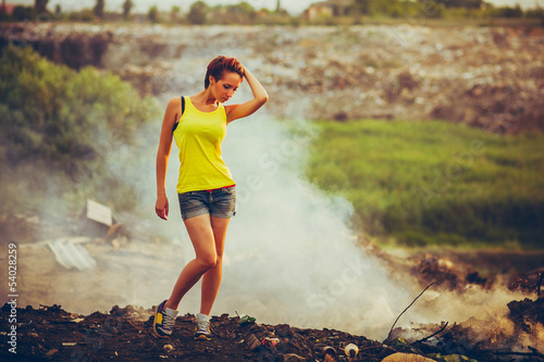 homeless young beautiful woman in a yellow tank top and denim sh