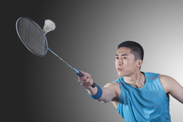 Young man playing badminton, hitting