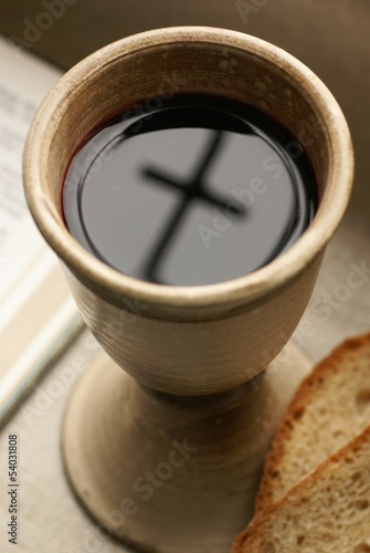Chalice with wine, piece of bread and open Bible.