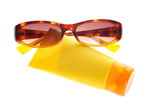 Sunglasses and sun lotion on white background