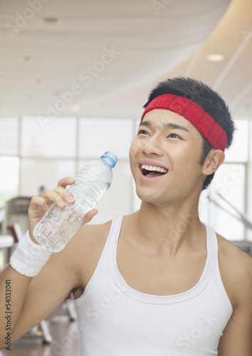 Portrait of smiling young man drinking from water bottle at the gym