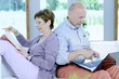 Seniorenpaar Best Ager mit Buch und Notebook