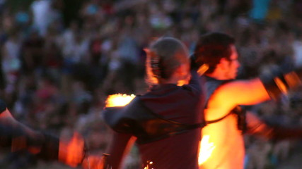 Men and woman dance with burning chain fire pois