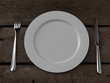 white plate, knife and fork on wooden table