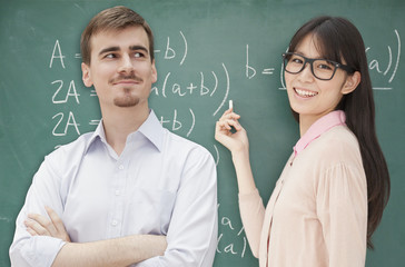 Two students doing math formula on the chalkboard, Beijing
