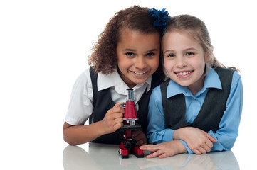 Young little school girls with microscope